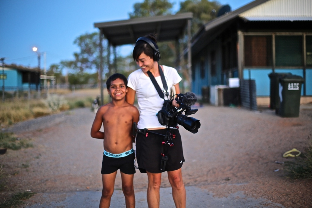 Young Indigenous boy next to film director in remote community.
