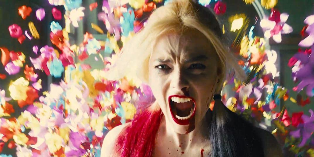 Margot Robbie screams at the camera against a background of flowers