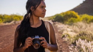Young Indigenous woman with camera on desert road, a product of Screenwest and West Coast Visions.