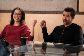 A man and a woman bump fists in an office setting