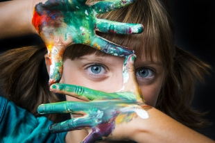 Little girl framing face with painted fingers